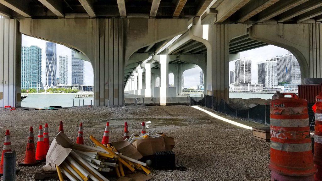 อุปกรณ์ก่อสร้างและกรวยจราจรวางระเกะระกะอยู่ที่พื้น ใต้สะพานริมน้ำ